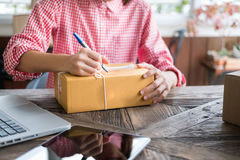 Start up small business owner writing address on cardboard box a. Young start up small business owner writing address on cardboard box at workplace. freelance Stock Photo
