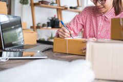 Start up small business owner writing address on cardboard box a. Young start up small business owner writing address on cardboard box at workplace. freelance Royalty Free Stock Photos