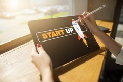 Start up spaceship on device screen. Business and finance concept. stock image