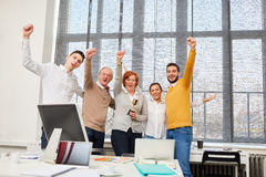 Start-up team cheering about their success. With winner trophy Stock Images