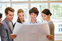 Start-up team looking at project plan Royalty Free Stock Image