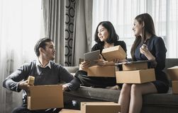 Start up team of online retailer packing boxes to send out. To customer Stock Photo