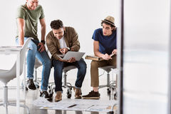 Start-up team trying to understanding business issues. What is it. Puzzled young men is pointing finger at laptop while his colleague are looking at screen with stock photos