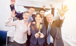 Start-up team with winner trophy. In success celebration royalty free stock images