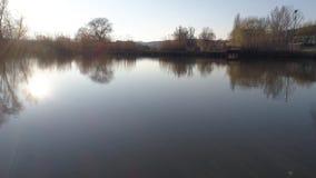 Start van lakeshore op een zonnige dag, voorzijde aan de zon, dichtbij een klein visserijmeer in Sarisap, Hongarije stock videobeelden