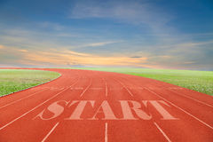Start written on Running track with green grass and blue sky whi Royalty Free Stock Images
