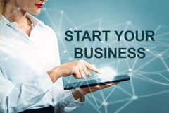 Start Your Business text with business woman. Using a tablet royalty free stock photography