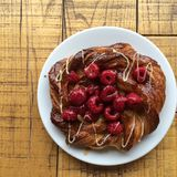 Start your day with homemade Gourmet danish pastry raspberry and icing on wood table. Start your day with homemade Gourmet danish pastry raspberry and icing on Royalty Free Stock Photography