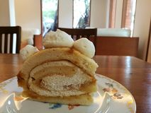 Start your day with homemade Gourmet pastry vanilla roll cake  top with cream cheese on vintage plate on wood table in the cafe wi Stock Photos