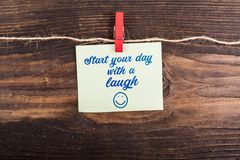 Start your day with a laugh. Write in sticky note with clothes pin and rope on wood Stock Photos