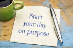Start your day on purpose. Inspirational handwriting on a napkin with a cup of coffee stock images