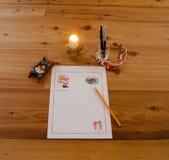 Starta att skriva brevet till Santa Claus på ljuset av en stearinljus Arkivfoto