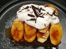 Starta din dag med hemlagad gourmet- bakelse att baka rostat brödöverkanten med bananen, piskad kräm, karamell, och choklad äter  Royaltyfri Fotografi
