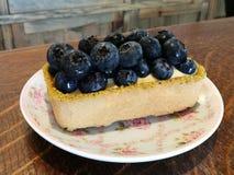 Starta din dag med ny blåbärostkaka för hemlagad gourmet- bakelse på tappningfloramaträtt på den wood tabellen i kafé med suddigh Royaltyfri Fotografi
