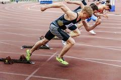 starta sprinterlöparemän att köra 100 meter Arkivbild