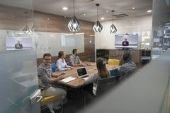 Starta upp gruppen för affärsfolk att delta i videokonferensappell royaltyfri foto