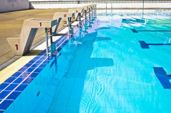 Startande plattformar med nummer för att simma lopp. Royaltyfri Foto