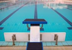 Startblokken in rij door het zwembad, selectieve nadruk Sprongplatform voor het zwemmen in zwembad en tribune backgroun royalty-vrije stock foto's