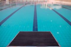Startblokken in rij door het zwembad, selectieve nadruk Sprongplatform voor het zwemmen in zwembad en tribune backgroun royalty-vrije stock foto