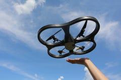 Starten eines quadrocopter in den Himmel mit den Händen stockfotografie