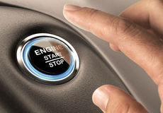 Starter Button. Car engine start and stop button with blue light and black textured background, close up and one finger Royalty Free Stock Photo