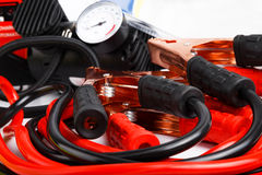 Starter cables and a pressure gauge for a car. Close up low angle on a coiled set of red and black starter cables or jump leads and a pressure gauge for a car Royalty Free Stock Photography