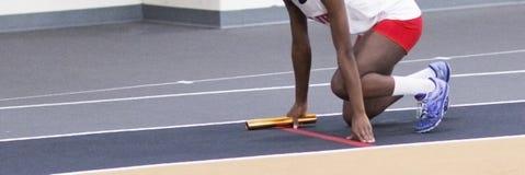 Startig femelle de coureur une course de voie de relais à l'intérieur image libre de droits