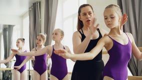 Starting ballet dancers are practising arm movements during ballet class in studio. Tutor professional ballerina