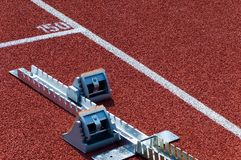 Starting block. On a red running track Royalty Free Stock Images