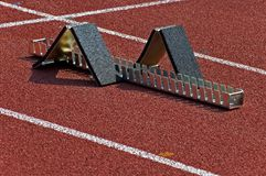 Starting block. On a red running track Royalty Free Stock Image
