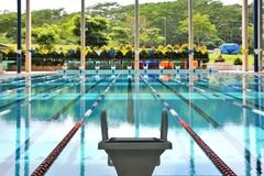 Starting block and empty swimming pool. A solitary starting block facing an empty olympic size swimming pool Stock Photos