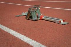 Starting blocks on red tartan running track Royalty Free Stock Photos