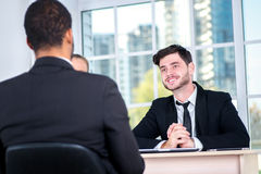 Starting a business meeting. Three successful business people si. Tting in the office and do business while businessman working at his desk Royalty Free Stock Photo