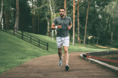 Starting day from morning jog. Full length of handsome young man in sports clothing jogging in park Stock Photos