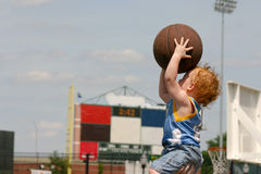 Starting early. Young male child ready to throw a basketball stock photography