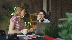 Starting enterpreneurs are finishing project, checking laptop and celebrating success with high five. They are happy and. Starting female enterpreneurs are stock footage