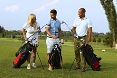 Starting game on golf course. Happy partners standing on golf course, choosing golf club from golfing kit, starting game Royalty Free Stock Image