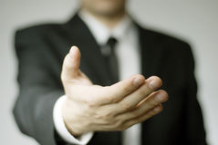 Starting a Handshake. Man in business attire offering his hand to shake or in help Stock Photo