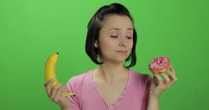 Starting healthy eating. Say no to junk food. Choice donut or banana to eat. Starting healthy eating. Say no to junk food. Beautiful sad young girl on a chroma stock video footage