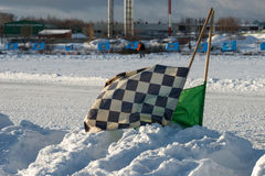 Starting judicial flags stuck in the snow. On the speedway sports track stock images