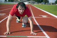 At the Starting Line. A young male adult is at the starting line of a track and field running event Stock Photos