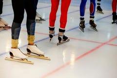 Starting line legs men athletes. Speed skaters in mass start stock photos