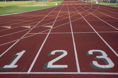 Starting line of a running track. Red running track with 1, 2, 3 numbers at the starting line and  green fields Stock Photography