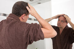 Starting new day. Man touching his hair while standing in front of the mirror Royalty Free Stock Photography