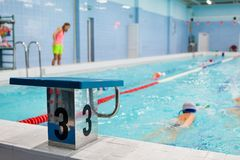 Starting platform with number three is in four lanes swimming pool for children groups. Kids do exercises with an instructor. Starting platform with number three stock image