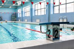 Starting platform with number two is in a swimming pool for children groups. Kids practice with instructor. Starting platform with number two is in swimming pool Stock Photo
