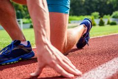 Starting point. Hand of sportsman on running track low start position. Runner ready to go close up. Ready steady go. Concept. At the beginning of great sport stock photo