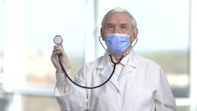 Starting to use stethoscope. Senior old doctor with a stethoscope in the hands on white windows background stock video footage