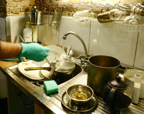 Starting to wash a dishes. Starting hand washing in the kitchen with gloves Royalty Free Stock Photography