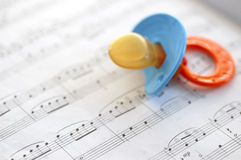 Starting young. Music lesson concept. One is never too young to appreciate musical arts. Closeup shot of pacifier and sheet music royalty free stock image